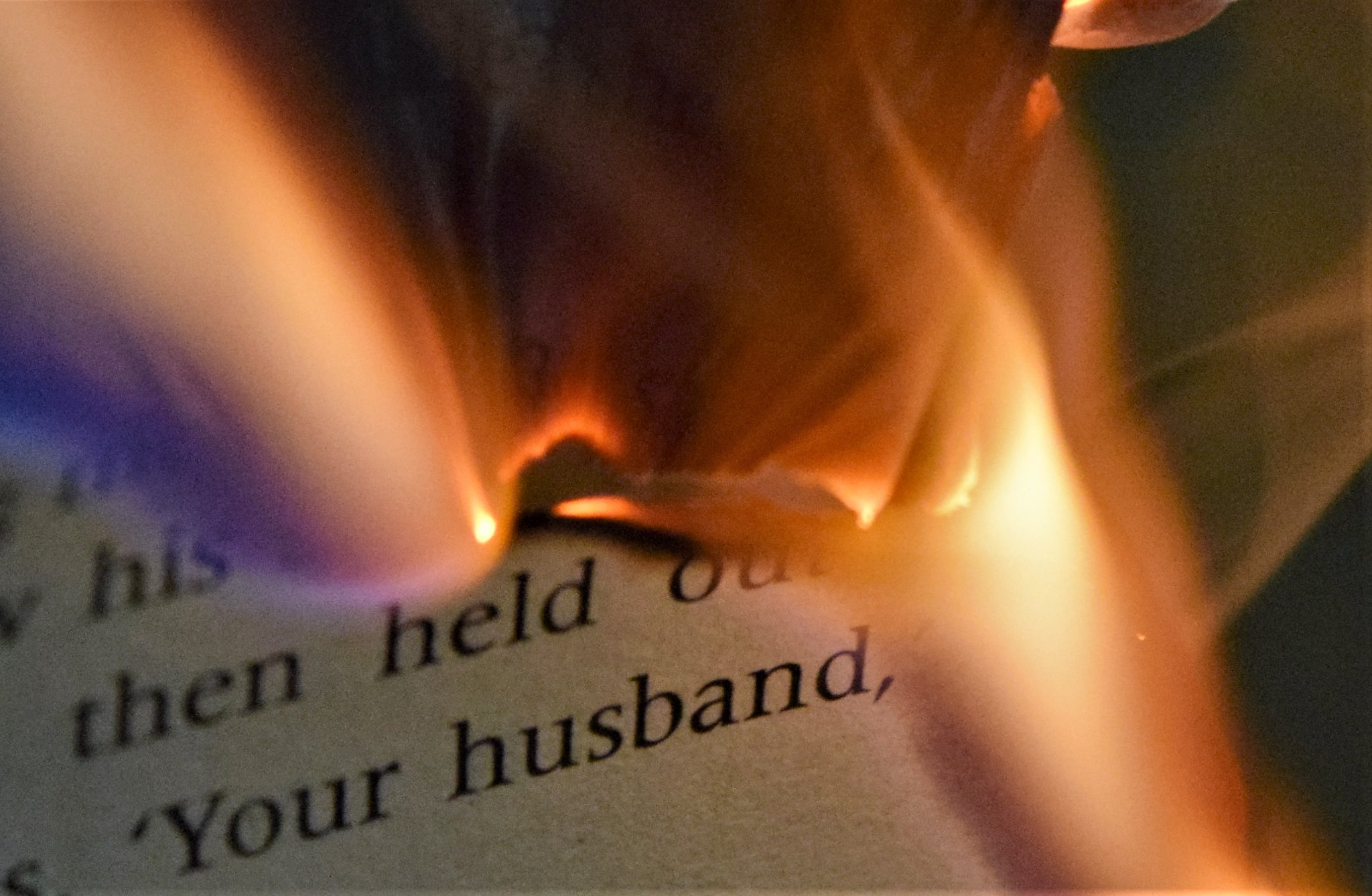 Pages of a book burning in a small fire
