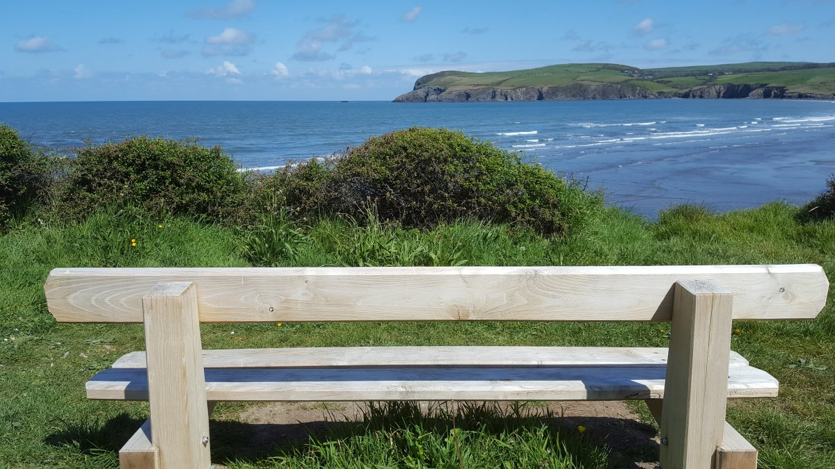 The back of a bench is in the foreground showing its view across a broad bay